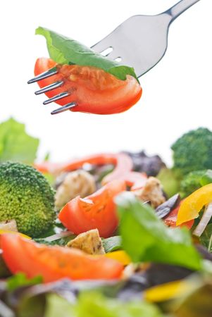 A healthy salad isolated on white with a fork holding a piece of lettuce and tomato. Stock Photo