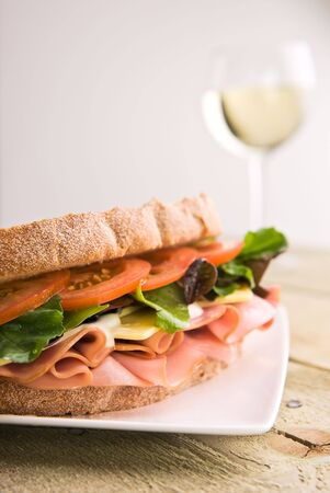 A gourmet sandwich with a glass of wine in the background. Stock Photo - 5069339