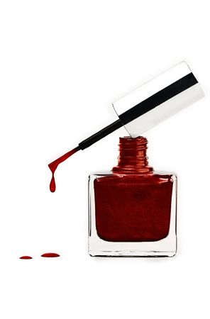 Sparkling red nail polish in a bottle with a dripping brush balanced on top.