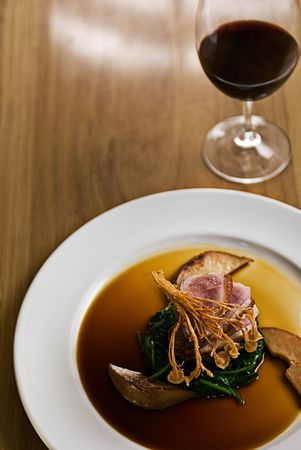 Crispy duck on a bed of spinach served with red wine in a restaurant. Stock Photo