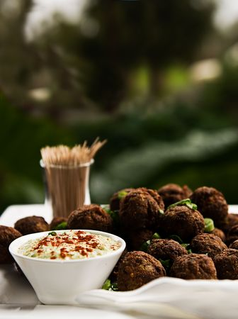 A platter of meatballs garnished with herbs, served on a platter with toothpicks and a dipping sauce.