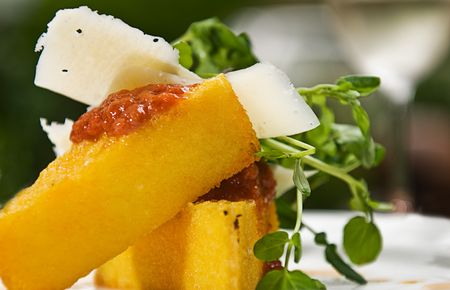 A serving of polenta with a tomato sauce, cheese and watercress, served with a glass of white wine. Stock Photo