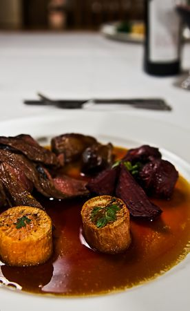 A dish of kangaroo meat with roasted beetroot and sweet potato in a gravy sauce.