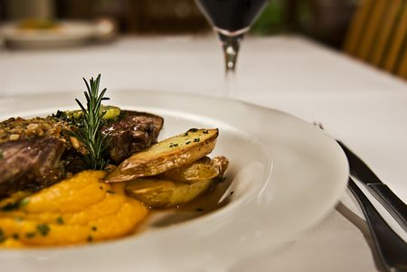 Meat, potato and pumpkin puree, served with red wine. Stock Photo