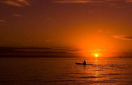 Kayaking at sunset in the ocean.