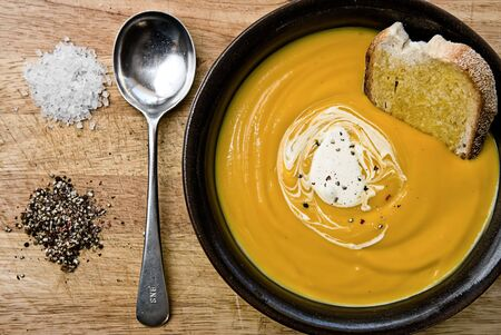 Pumpkin soup in a bowl with toast and cream with a spoon and salt and pepper on the side.