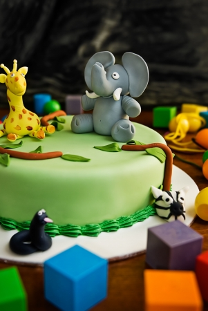 girotondo bambini: Jungle torta di compleanno a tema con un elefante e la giraffa in cima, circondato da mattoni. Archivio Fotografico