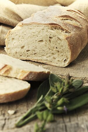 Freshly baked loaf of bread, just sliced with fresh herbs. Stock Photo