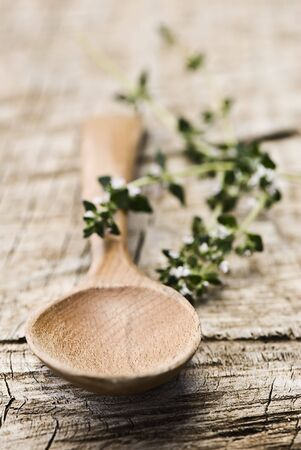 Rustic wooden spoon with fresh herbs on an old wooden board Stock Photo