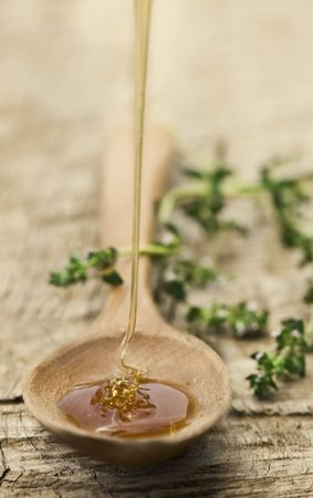 Fresh honey being poured into a rustic wooden spoon