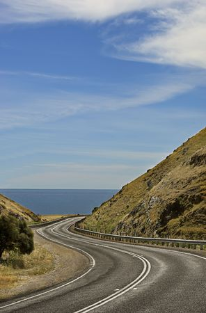 A scenic and winding coastal road between mountains, leading to the ocean. photo