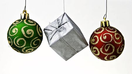 Brightly coloured sparkling and shiny new christmas baubles in a row isolated on white. Stock Photo