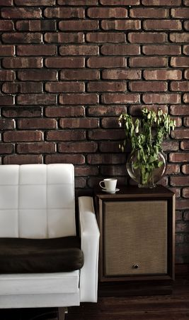 Retro styled lounge room showing a couch, speakers, cup, plant on wooden floor and a brick wall. photo