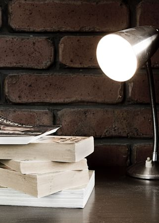 Collection of books sitting on a table under a lamp