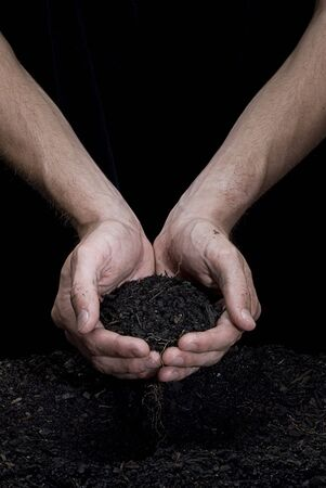 Male hands holding some fresh soil. Hands are dirty.