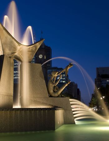 A Water Fountain in the city lit with lights at dusk Stock Photo