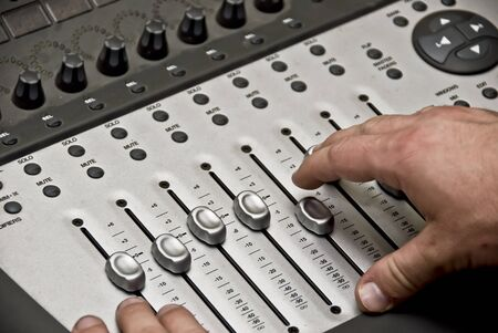 View of a man working the audio recording equipment in a music recording studio. photo
