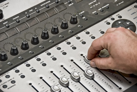 View of a man working the audio recording equipment in a music recording studio.