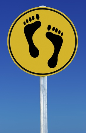 Footprints on a road sign isolated on a blue graduated sky.