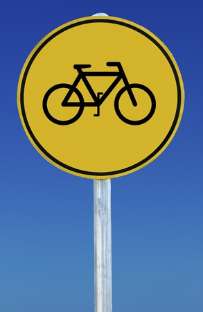 Circular yellow sign on blue sky background. Sign features a picture of a bicycle photo