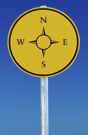 Compass symbol on a yellow sign on a blue background photo