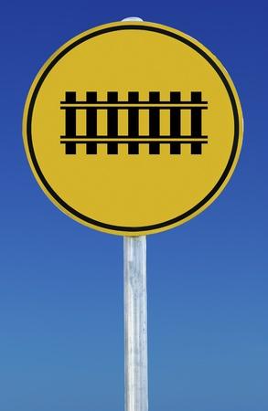 A train tracks road sign isolated on a blue graduated sky. photo