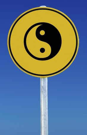 A Yin Yang sign isolated on a blue graduated sky. photo