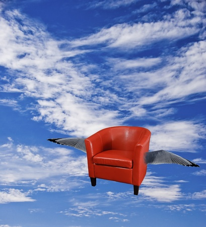 Flying red leather armchair with wings flying through the sky. Stock Photo - 9138966
