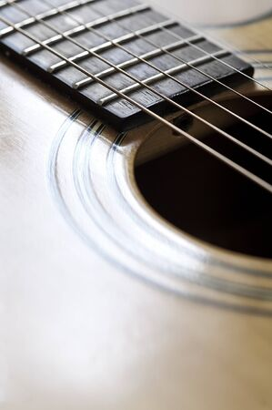 Close up view of the strings and body of an acoustic guitar. photo