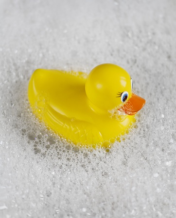 Bathtime fun with a yellow rubber ducky in a bathtub full of water and bubbles. Stock Photo