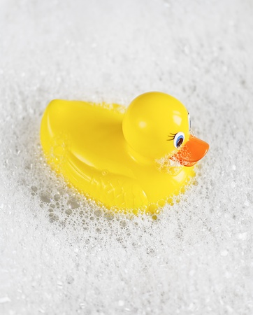 Bathtime fun with a yellow rubber ducky in a bathtub full of water and bubbles. Stock Photo - 9491474