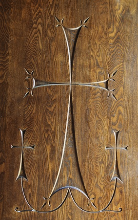 Carving of 3 cross with one large central cross joined to 2 smaller crosses on either side. Carved into an antique woodern door. photo