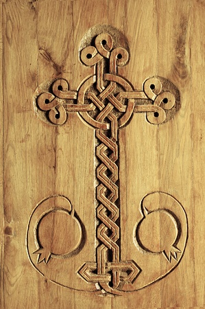 armenian: Carving of a cross in a door of an ancient Armenian Church. Carving features a intricate cross and pomegranates. Stock Photo
