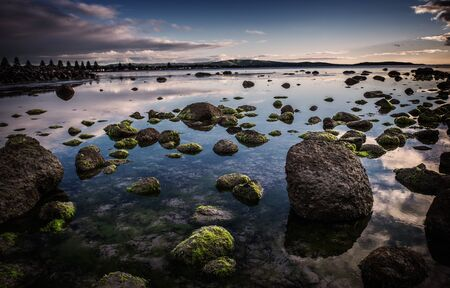 Moss covered rocks at sunrise  The water is still allowing both reflections of the sky and being able to see through to the bottom of the ocean Stock Photo - 17692700