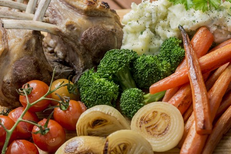 Roast Rack of Lamb with roasted mixed vegetables, onions, carrots, tomatoes, broccoli and mashed potato