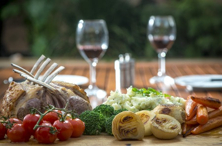 Roast Rack of Lamb with roasted mixed vegetables, onions, carrots, tomatoes, broccoli and mashed potato photo