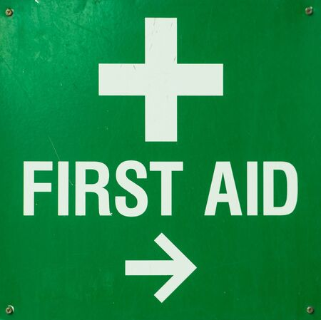 aid: Green metal First aid Sign screwed to a wall and pointing towards the first aid room