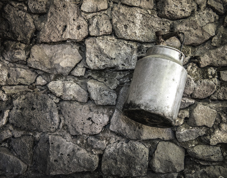 stone wall: An old fashioned milk tin hanging from an ancient stone wall