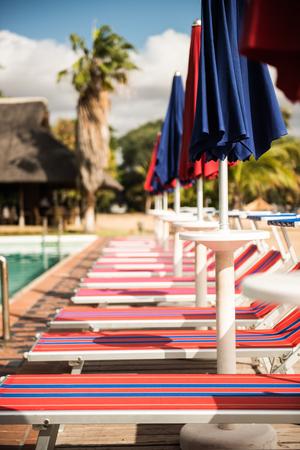 Row of Italian sun beds next to the resort pool Stock Photo