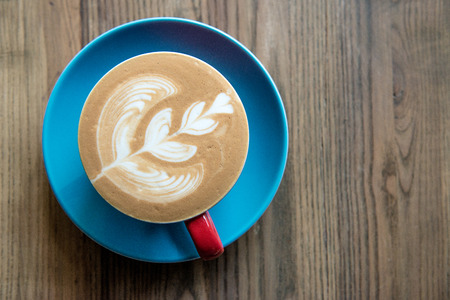 Fresh cup of coffee with a beautiful design on top sitting on a wooden table