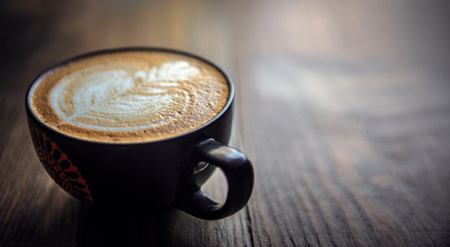 Fresh cup of Hot coffee with a beautiful design in the milk on a wood table Stock Photo