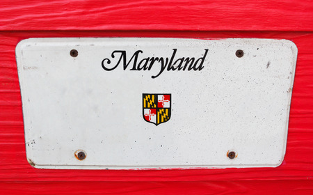 license plate: White license plate of Maryland, America on red wood background. Stock Photo