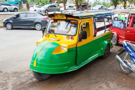 MOTORIZADO: Ayutthaya Tailandia - 30 de julio de 2015: amarillo y verde rickshaw automático, motorizado de tres ruedas parque a esperar los viajeros en Wat Chaiwatthanaram.