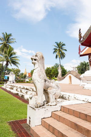 White lion sculpture in front of Ubosot Wat Phumin Nan, Thailand Side view