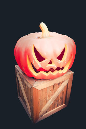 hollows: Scary smile of Halloween pumpkin on wooden box, black background, Isolated.