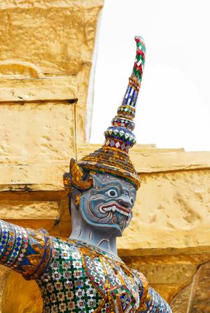 in wat phra kaew: Head of giant demon statue on golden pagoda at Wat Phra Kaew, Bangkok, Thailand. Stock Photo