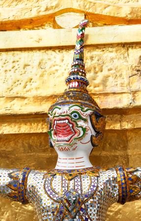 in wat phra kaew: Head of giant demon statue on golden stupa at Wat Phra Kaew, Bangkok, Thailand. Stock Photo