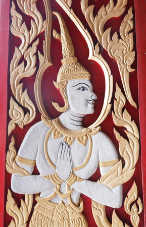 male angel: Carving male angel on wooden door in Thai temple. Stock Photo