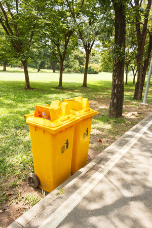 public waste: Yellow plastic bin in the public park. Stock Photo