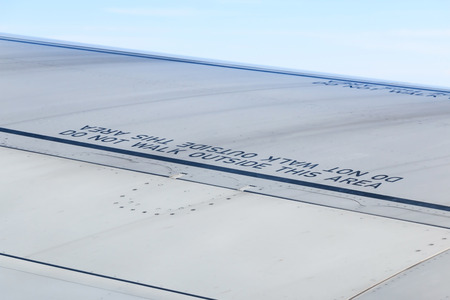 Caution word, Do not walk outside this area on wing of commercial airplane.